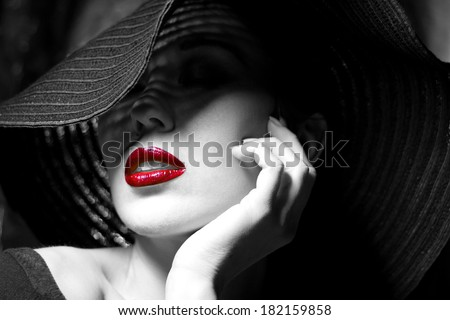 Portrait of mysterious beautiful young woman with wonderful skin texture  in  black hat. Trendy glamorous fashion makeup. Sensual red lips. Black and white image. Art photo - stock photo