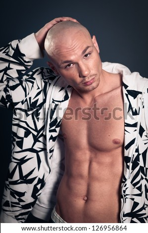 Portrait of naked athletic man posing over gray background - stock photo