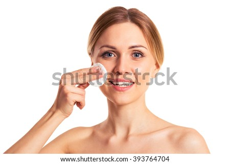 Portrait of naked beautiful young woman clearing her face with a sponge and smiling, isolated on a white background - stock photo