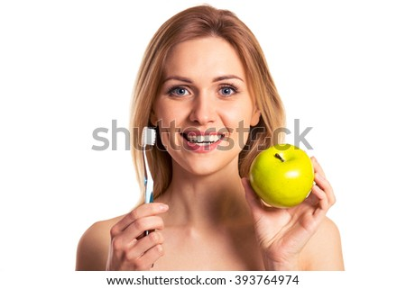 Portrait of naked beautiful young woman smiling, holding a toothbrush and an apple, isolated on a white background - stock photo