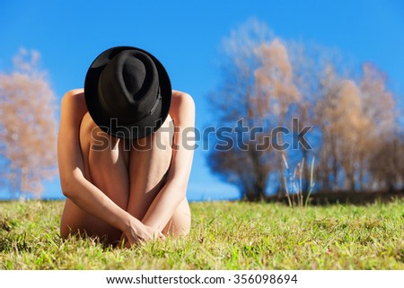 portrait of naked girl with hat crouched, outdoors - stock photo