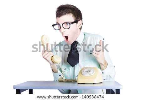 Portrait of nerdy young businessman shouting into receiver of retro telephone, white background