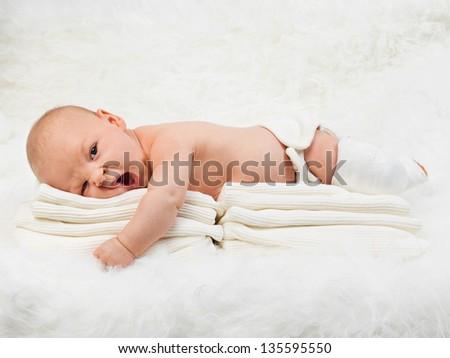 Portrait of new born baby boy yawning on a fur blanket - stock photo