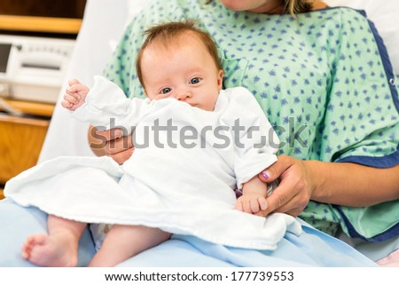 Portrait of newborn baby girl sitting with mother lap in hospital room