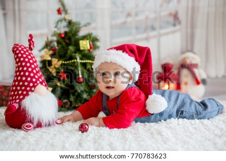 Portrait of newborn baby in santa clothes and christmas hat lying on the ground
