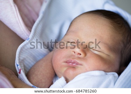 Portrait of newborn in his mother arms
