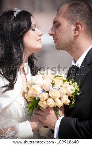 Portrait of newly married couple looking at each other and holding bouquet - stock photo