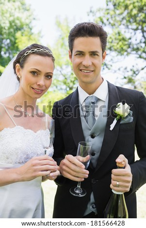 Portrait of newlywed couple having champagne in garden