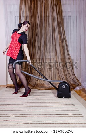 Portrait of nice housewife doing housework with vacuum cleaner - stock photo