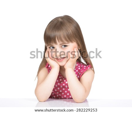 Portrait of nice little girl in a pink dress who sits at the table and smiles, on a white background.