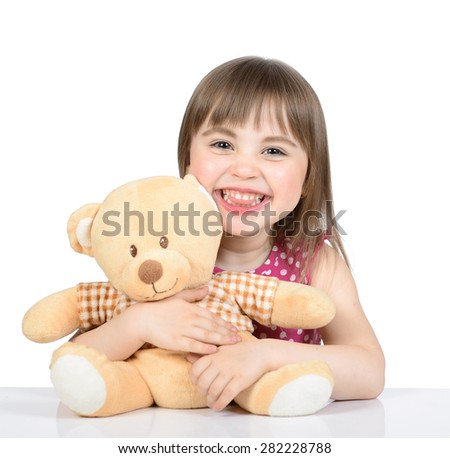 Portrait of nice little girl in a pink dress who sits at the table with a toy bear and smiling on a white background.