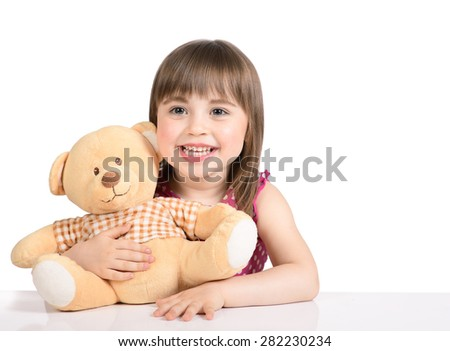 Portrait of nice little girl in a pink dress who sits at the table with a toy bear on white background.