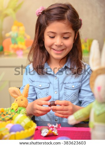 Portrait of nice little girl opening small chocolate egg, having fun at home, preparing to happy religious spring holiday, Easter