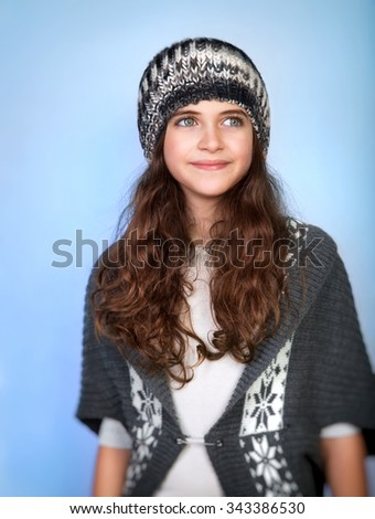 Portrait of nice stylish teen model wearing warm hat and sweater, posing over blue background, dreamy looking in side, winter fashion for girls