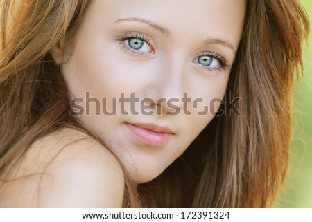 Portrait of nice young woman, against background of summer green park. - stock photo