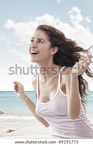 Portrait of nice young woman  having good time on the beach - stock photo