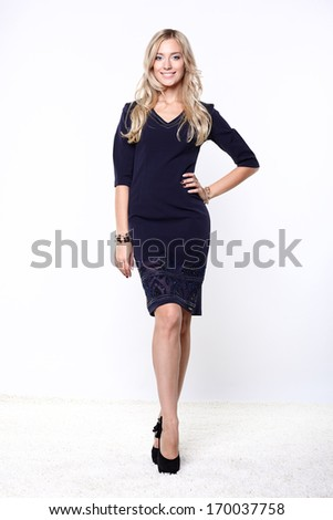 Portrait of nice young woman in a dark blue dress. - stock photo