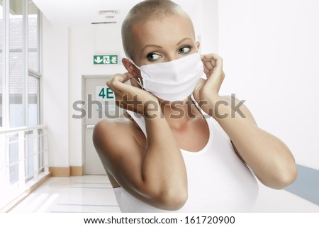 Portrait of nice young woman in surgery mask on color back