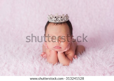 Portrait of nine day old sleeping newborn baby girl. She is wearing a rhinestone crown and is posed with her chin in her hands. - stock photo