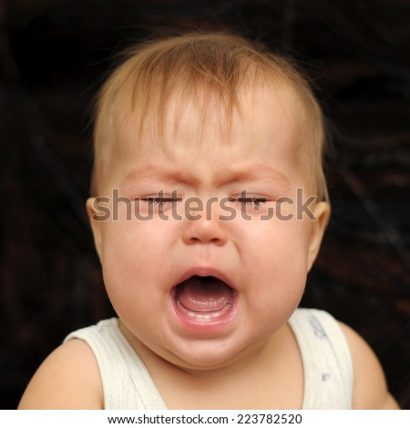 Portrait of nine month baby crying very emotionally - stock photo