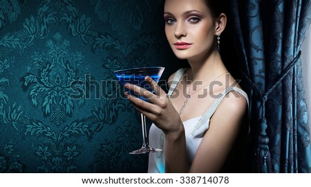 Portrait of noble beautiful woman with martini glass on damask wallpaper background. Banner for interior design studio. - stock photo