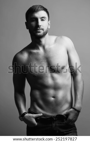 Portrait of nude muscular handsome fitness male model in jeans.