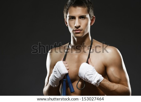 Portrait of nude sportsman keeping a string with his hands wrapped with elastic bandage, isolated on black - stock photo