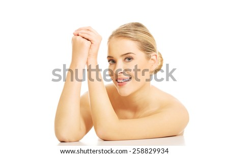 Portrait of nude woman clenching hands, sitting at the desk.