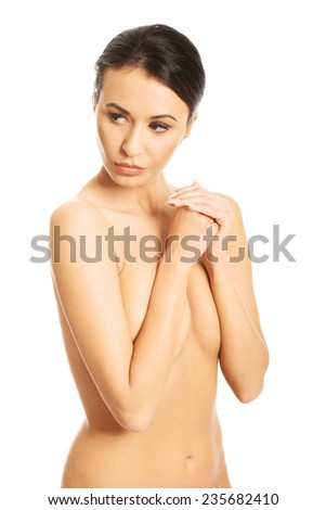 Portrait of nude woman covering her breast and looking away.