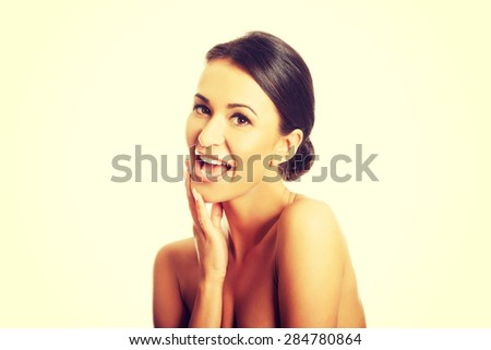 Portrait of nude woman laughing loud, looking at the camera.
