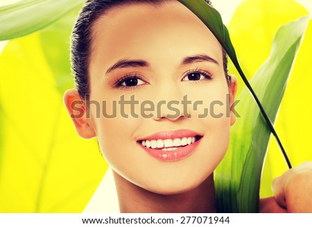 Portrait of nude woman with green leaves. - stock photo