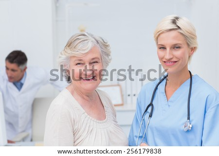 Portrait of nurse and senior patient smiling in clinic - stock photo