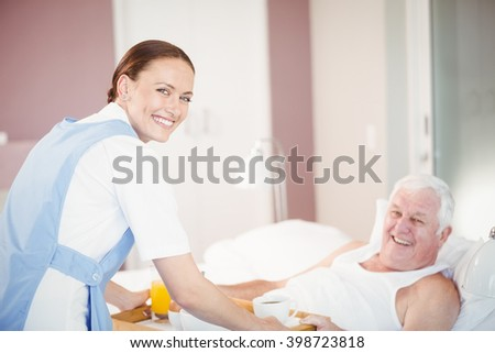Portrait of nurse offering breakfast to senior man lying on bed at home