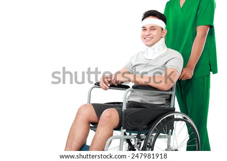 portrait of nurse pushing young patient in wheelchair on white background - stock photo
