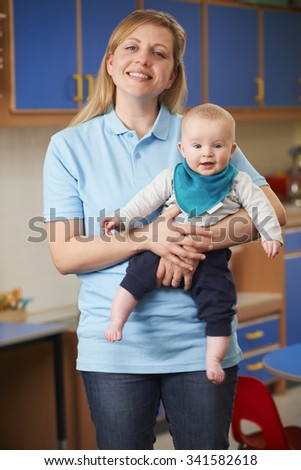 Portrait Of Nursery Worker Holding Baby