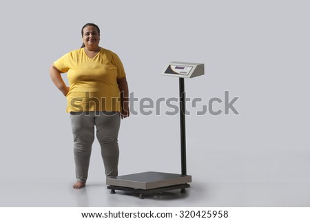 Portrait of obese woman with weighing scale - stock photo