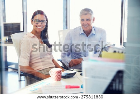 Portrait of office colleagues smiling to camera - stock photo