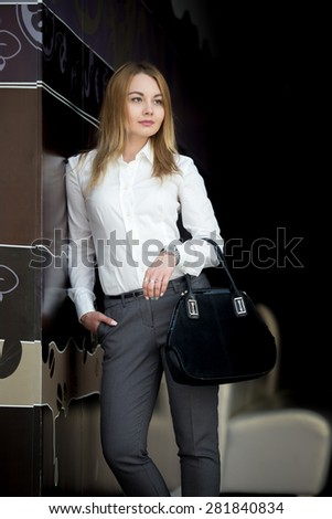 Portrait of office employee, attractive confident young business woman in white shirt with pensive serious expression - stock photo