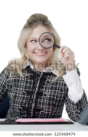 Portrait of office girl smiling while holding magnifying glass - stock photo