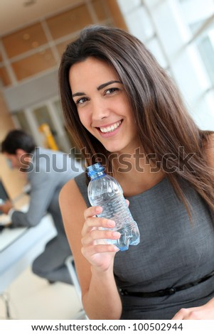 Portrait of office worker drinking water from bottle - stock photo