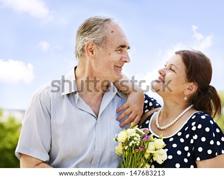 Portrait of  old couple with  bouquet at summer  outdoor.