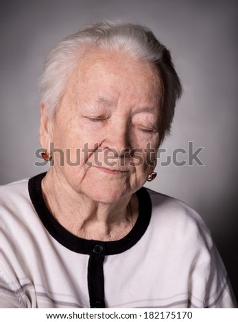 Portrait of old pensive woman with closed eyes  on a gray background