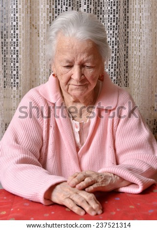 Portrait of old sad woman at home - stock photo