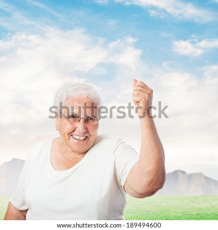 portrait of old woman doing a winner gesture