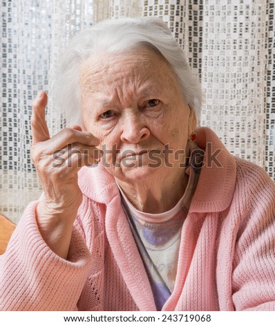 Portrait of  old woman in angry gesture at home