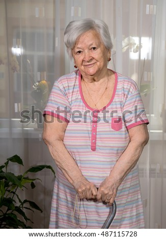 Portrait of old woman standing with a cane at home