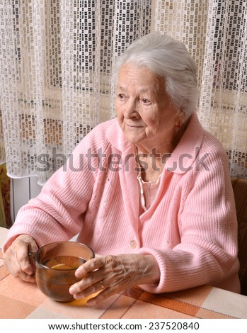 Portrait of old woman with cup of tea at home - stock photo