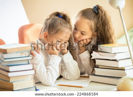 Portrait of older sister soothing younger one while doing homework - stock photo