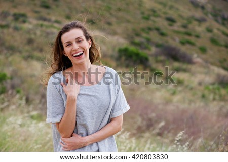 Portrait of older woman laughing in field  - stock photo