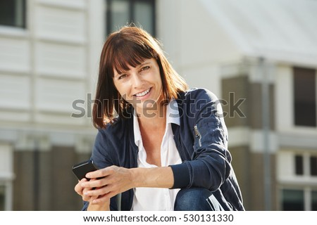Portrait of older woman sitting outside with smart phone in city